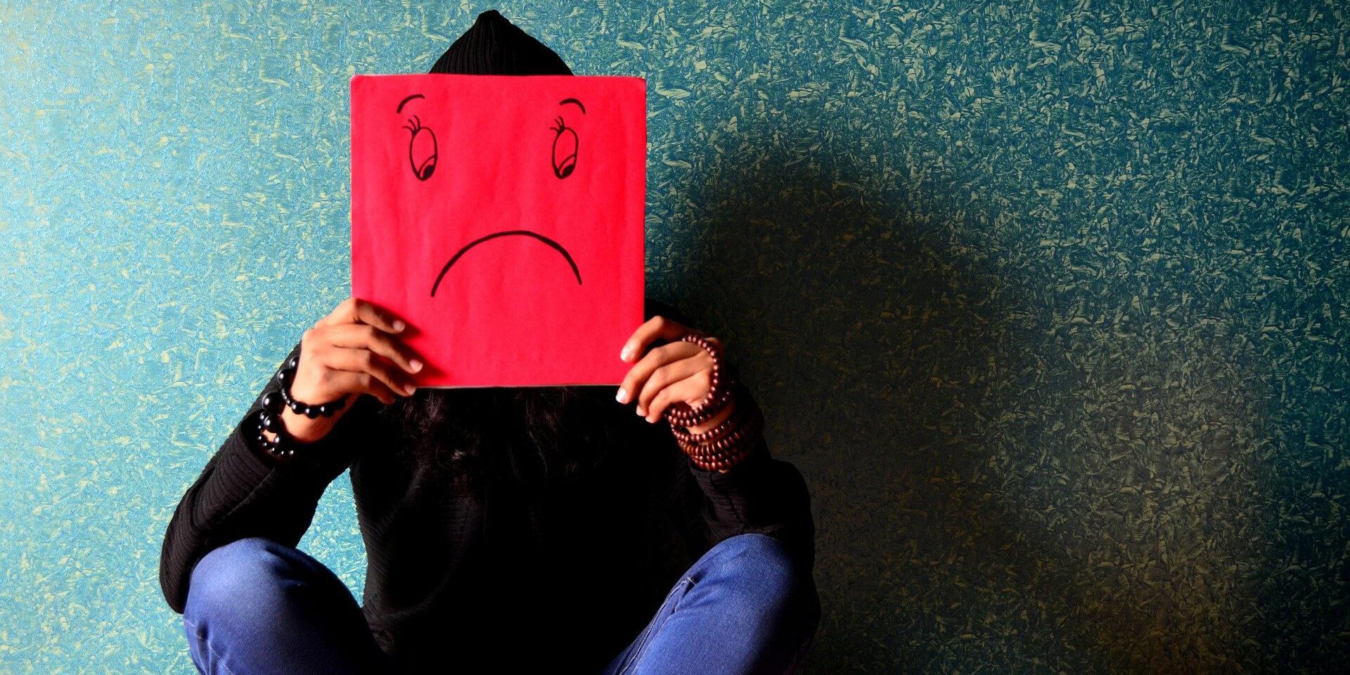 Ein Mensch hält ein trauriges Emoji vor sein Gesicht.