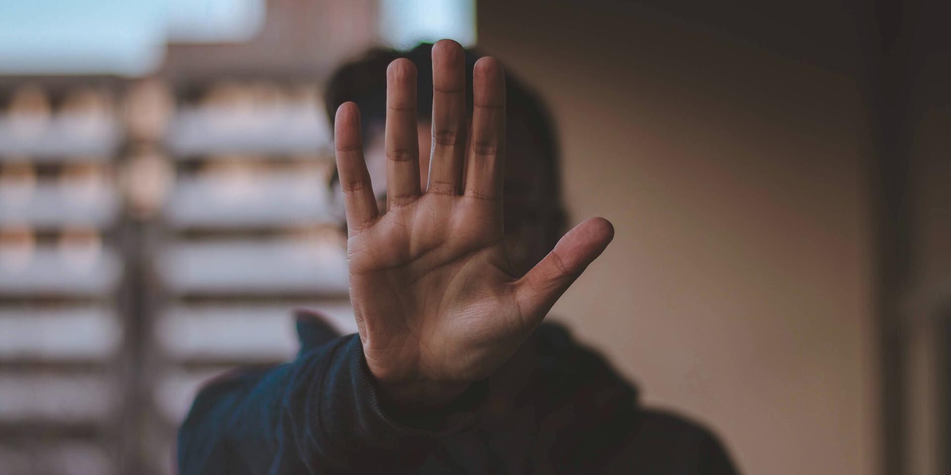 Eine Person streckt abwehrend ihre Hand vors Gesicht.
